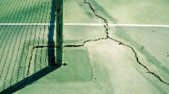 Square net posts cause radiating cracks ruining court.